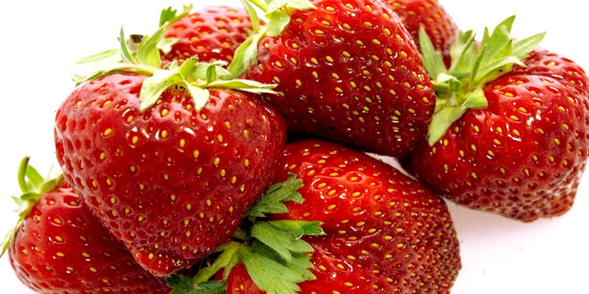 Die Erdbeere wird als Garnitur in zwei Hälften geschnitten.